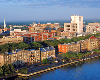 A photo at sunset of the riverfront in Savannah, Georgia (red brick buildings surrounded by greenery, parallel to a blue river and blue sky).