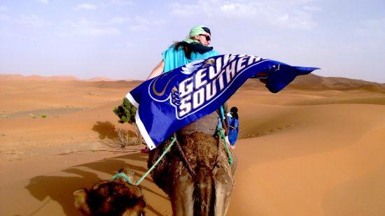 A Georgia Southern student riding a camel flying a blue Georgia Southern flag behind him like a cape