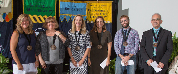 a group of faculty proudly wearing their award medallions