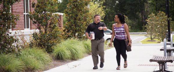 two people talk while walking on sidewalk next to a brick building