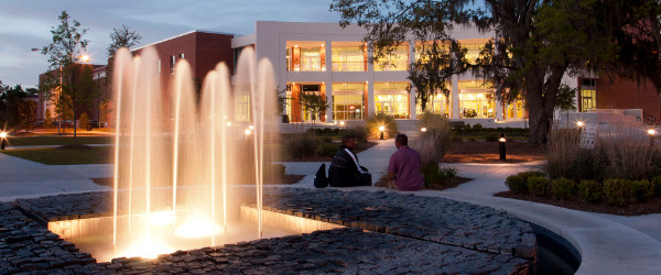 people sit by a lighted fountain in front of a lighted modern building at dusk